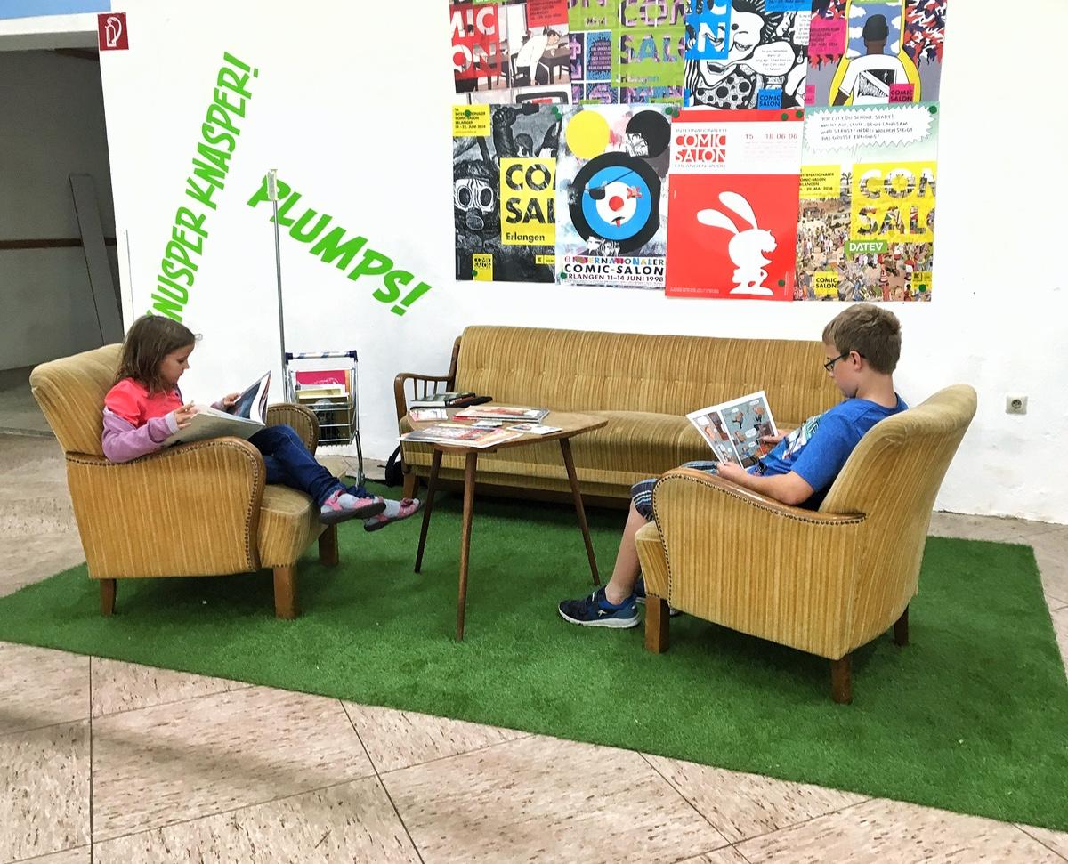 Nelly und Mattis schmökern in der Leseecke im Comic-Markt Wiedensahl.