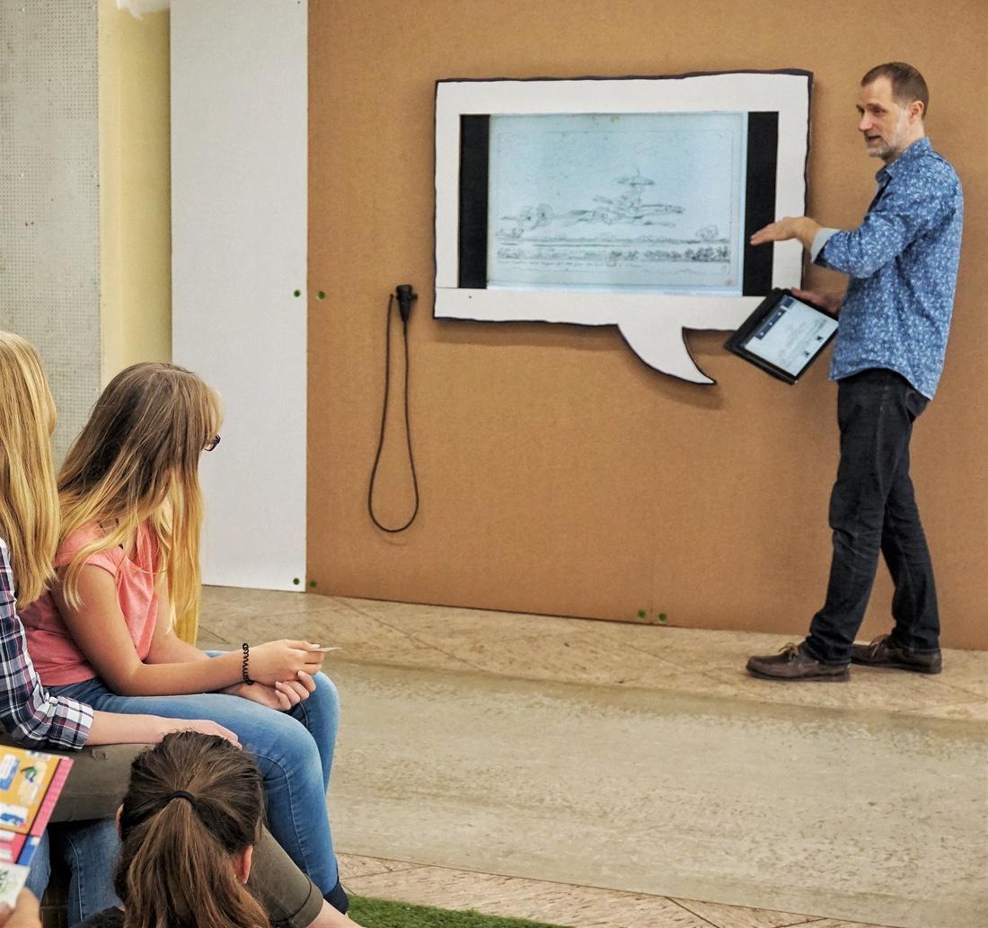 Kurator Darjush Davar erläutert Schülern der IGS Helpsen anhand von Bildbeispielen die wesentlichen Gestaltungsmittel der Comic-Kunst.